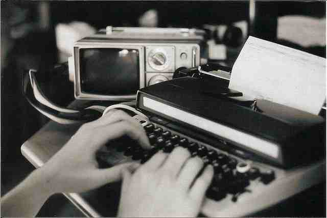 A persons hands on a typewriter keyboard